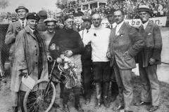 12 czerwca 1921 r., Opelbahn Rüsselheim: Fritz von Opel wygrywa z nową maszyną do wyścigów torowych Opla (198 cm3). Po lewej obok Fritz von Opel Opel kierowca Fritz Knappke, po prawej w białym swetrze Heinrich Herth